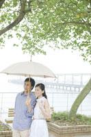 傘を差して水辺を散歩するカップル