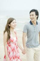 手を繋いでビーチを散歩するカップル 24031000313A| 写真素材・ストックフォト・画像・イラスト素材|アマナイメージズ
