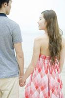 ビーチで手を繋ぐカップル