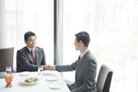 レストランで握手をするビジネスマン