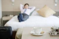 ホテルの部屋で寛ぐビジネスマンとティーセット