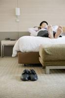 ホテルのベッドで裸足で寛ぐビジネスマン