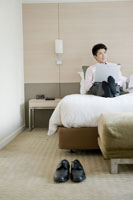 ホテルのベッドでパソコンを操作するビジネスマン