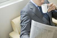 コーヒーを飲みながら新聞を読むビジネスマン