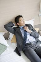 ベッドの上でネクタイを緩めるビジネスマン