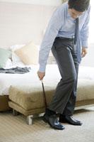ホテルの部屋で革靴を履くビジネスマン