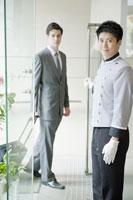 ホテルに入るビジネスマンとドアマン