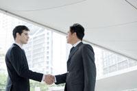 オフィス街で握手をするビジネスマン