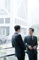 オフィス街で立ち話をするビジネスマン