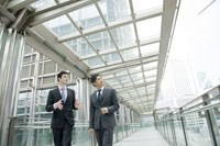 オフィス街を話しながら歩くビジネスマン