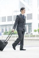 キャリーバッグを運ぶビジネスマン 24031000501  写真素材・ストックフォト・画像・イラスト素材 アマナイメージズ