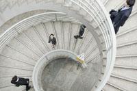 螺旋階段を歩くビジネスマンとビジネスウーマン