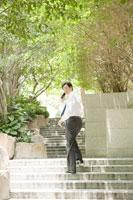 携帯電話で話しながら階段を登るビジネスマン