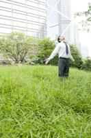 オフィス街の公園で深呼吸をするビジネスマン