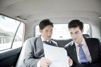 タクシーで商談をするビジネスマン
