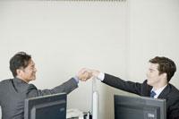オフィスで握手をするビジネスマン