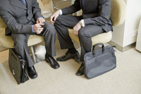 鞄を床に置いて椅子に座るビジネスマン