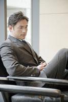 椅子に座って足を組むビジネスマン