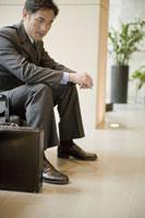 ロビーで椅子に座るビジネスマン