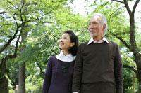 木立の中で微笑むシニアカップル 24032000001A| 写真素材・ストックフォト・画像・イラスト素材|アマナイメージズ