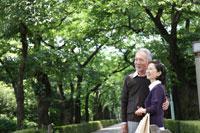 木立の中で微笑むシニアカップル 24032000003| 写真素材・ストックフォト・画像・イラスト素材|アマナイメージズ