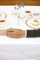 テーブルの上でつながれたシニアカップルの手元 24032000032  写真素材・ストックフォト・画像・イラスト素材 アマナイメージズ