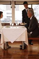 ディナーをサーブされるシニアカップル