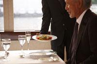ディナーをサーブされるシニア男性