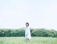 芝生の上を歩く女性
