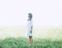 芝の上で遠くを見つめる女性