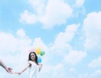 風船を持って手を繋ごうとする女性 24037000030| 写真素材・ストックフォト・画像・イラスト素材|アマナイメージズ