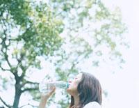 森の中でミネラルウォーターを飲む女性