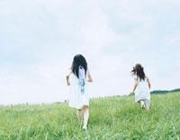 芝の上で追いかけっこをする女性 24037000059| 写真素材・ストックフォト・画像・イラスト素材|アマナイメージズ