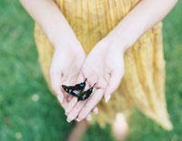 蝶々を持った女性の手元