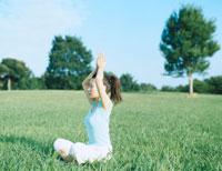 芝の上でヨガをする女性