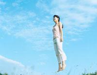 青空の下でジャンプする女性