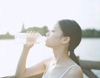 川辺でミネラルウォーターを飲む女性