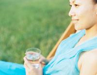 デッキチェアの上でグラスを持つ女性