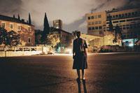 夕暮れの駐車場に立っている女性の後姿