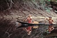 丸木舟で細い川を下降する少年たち