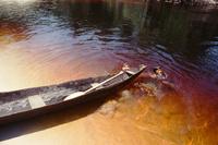 丸木舟と川の中で遊ぶ子ども