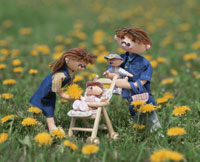 たんぽぽの咲く中を散歩する家族