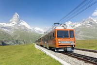 マッターホルンとリッフェルアルプ付近の森林限界を走るゴルナーグラート鉄道の電車