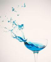 グラスから飛びちる青いカクテル 25609001180| 写真素材・ストックフォト・画像・イラスト素材|アマナイメージズ