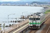 海辺の駅に停車する室蘭本線のキハ40系普通気動車