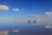 水面が鏡のようになったウユニ塩湖を走る自転車