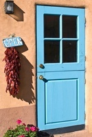 A turquoise-painted wooden stable-style door in an adobe wal