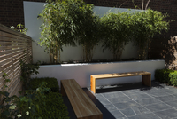 Compact, contemporary town garden patio in the Islington area of North London, UK, designed by Modular. With retaining wall cont