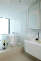 Bath on raised platform with champagne bottle, glasses and candle in UK show home