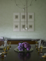 Dining table with floral display in residential home, Italy